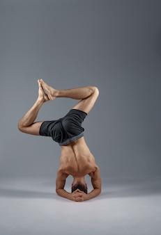 Yoga maschile in piedi sulla testa e sui gomiti, vista posteriore, meditazione, muro grigio uomo forte che fa esercizio yogi, allenamento asana, massima concentrazione, stile di vita sano