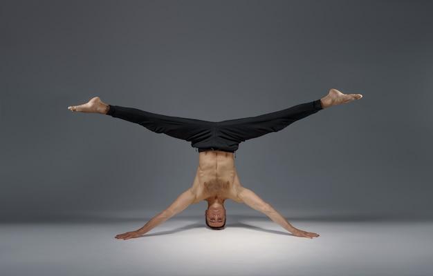 Yoga maschile in piedi sulla testa e sulle mani, meditazione, muro grigio uomo forte che fa esercizio yogi, allenamento asana, massima concentrazione