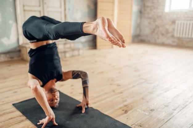 Yoga maschile si leva in piedi sulla testa in palestra