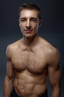 Yoga maschile con corpo muscoloso sul muro grigio uomo forte yogi in studio, formazione asana, massima concentrazione, stile di vita sano