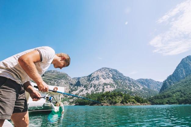 Il giovane adulto maschio cattura un pesce durante la filatura di uno stagno di acqua pura con splendide viste sulle montagne