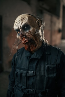 Zombie maschio che cammina nella fabbrica abbandonata