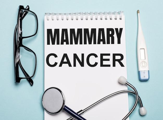 Cancro alla mammella scritto su un blocco note bianco accanto a uno stetoscopio, occhiali e un termometro elettronico su una superficie azzurra