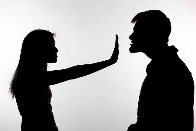 Uomo che abusa della donna, silhouette su uno sfondo bianco.