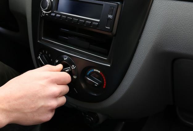 Uomo che regola il sistema del condizionatore d'aria in auto moderne, primo piano