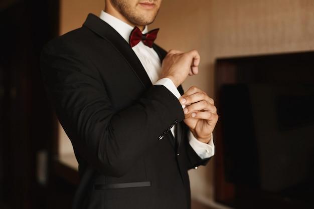 Un uomo che si aggiusta i gemelli sulla manica primo piano di eleganti mani maschili preparazione del giovane sposo