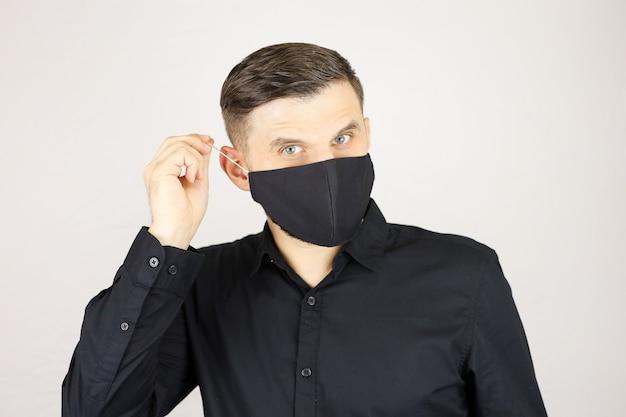 Un uomo regola una mascherina medica nera su sfondo bianco