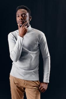 Uomo di aspetto africano abbigliamento alla moda fiducia in se stessi sfondo scuro