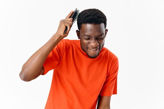 Aspetto africano dell'uomo con un pettine nelle sue mani parrucchiere per la cura dei capelli