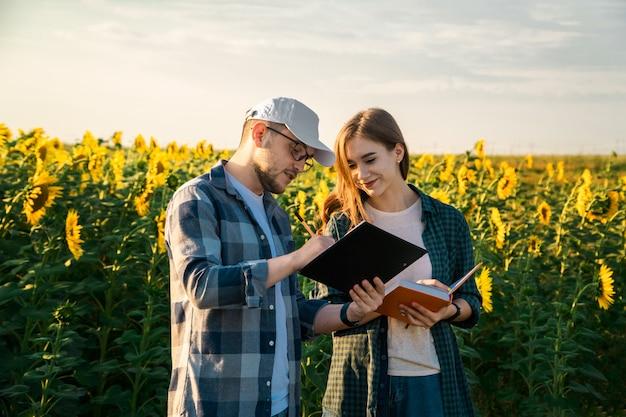 Agronomo di uomo che insegna al giovane studente nel campo di girasole