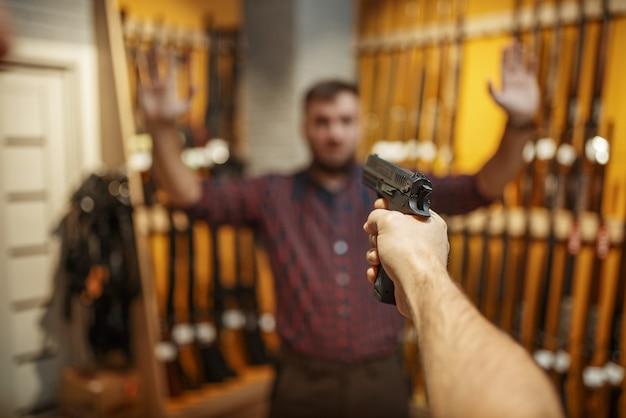 L'uomo mira con una nuova pistola sul venditore nel negozio di armi.