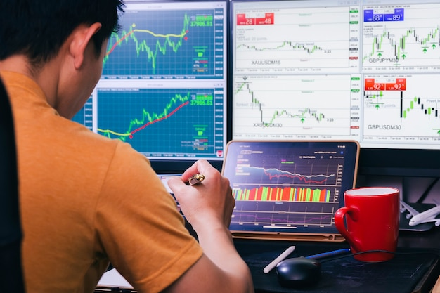 Grafico del mercato azionario forex di analisi dell'uomo per la vendita o l'acquisto di ordini di concorrenza di trading per trarre profitto nella notte a casa
