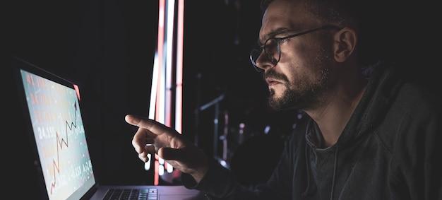 Un uomo che analizza i grafici del mercato azionario, i dati finanziari su una scheda elettronica.