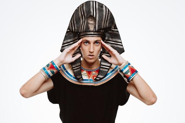 Uomo in antico costume egiziano preoccupato di toccare le tempie su bianco