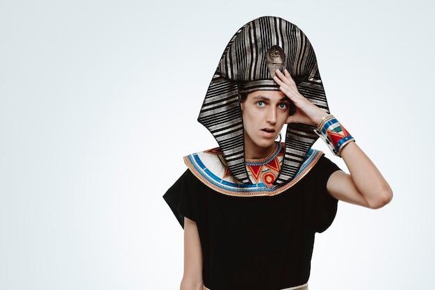 Uomo in antico costume egiziano confuso e preoccupato che tiene la mano sulla testa per errore su bianco