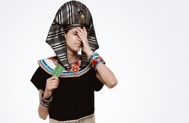 Uomo in costume egiziano antico che tiene gli occhi a cono della carta di credito con la mano con l'espressione delusa su bianco