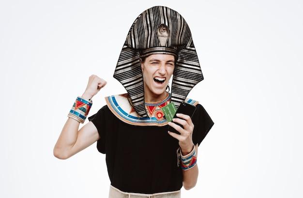 Uomo in costume egiziano antico che tiene smartphone e carta di credito che stringe il pugno eccitato e felice che si rallegra del suo successo su bianco