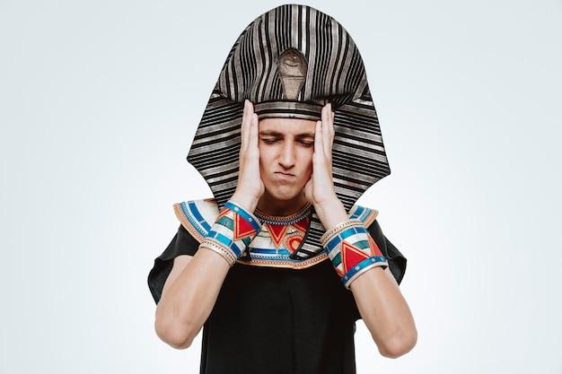 Uomo in antico costume egiziano che sembra indisposto e infastidito tenendosi per mano sulla testa su bianco