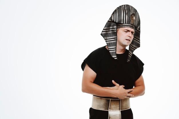 Uomo in antico costume egiziano che sembra malato toccando la pancia che soffre di dolore su bianco