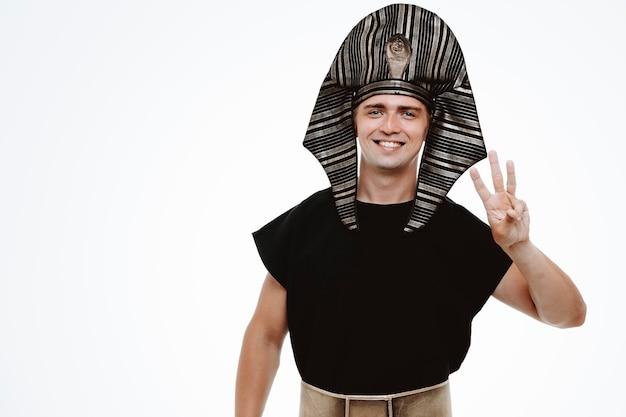Uomo in antico costume egiziano che mostra il numero tre rivolto verso l'alto con le dita su bianco