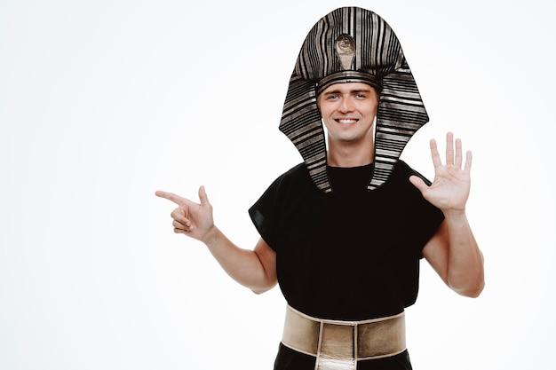 Uomo in antico costume egiziano sorridente che mostra il numero cinque con il palmo che punta con il dito indice di lato su bianco