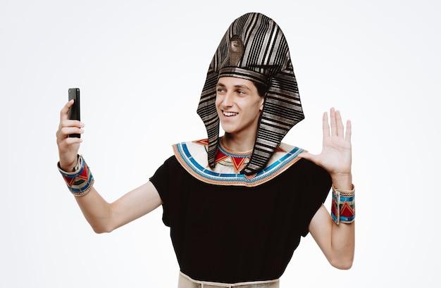 Uomo in antico costume egiziano che si fa selfie usando lo smartphone sorridendo felice e positivo che saluta allegramente con la mano su bianco