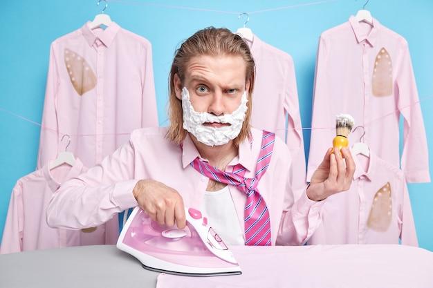 L'uomo applica la schiuma con la spazzola per radersi i ferri da stiro vestiti a casa pone vicino all'asse da stiro vestito in camicia e cravatta. routine quotidiana delle pulizie. concetto di vita domestica