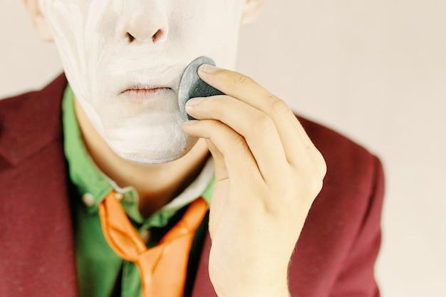 L'uomo si trucca, il clown si sta dipingendo la faccia