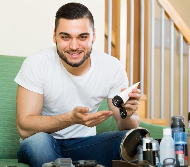 Uomo che applica la crema facciale a casa