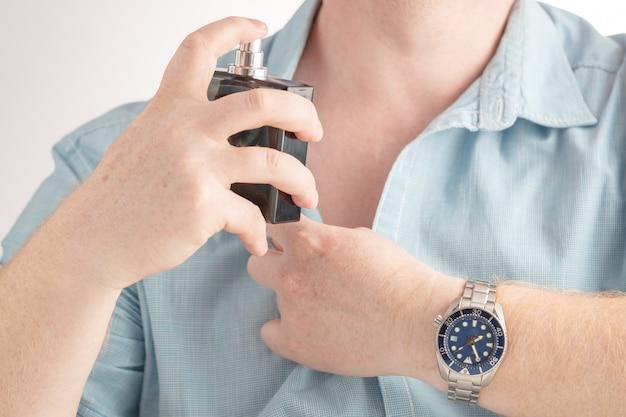 Equipaggi l'applicazione del profumo sul suo collo su bianco