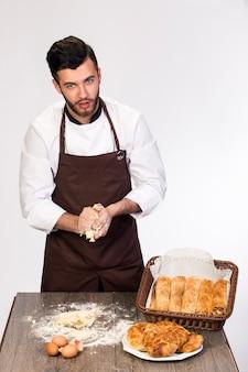 Un uomo in un grembiule prepara la pasta per la cottura, cook modello su un muro bianco impasta la pasta sul tavolo decorato con prodotti da forno