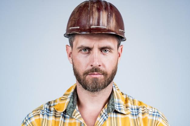 Architetto uomo con sguardo serio. ragazzo indossa l'uniforme da lavoratore. bel costruttore in casco. l'uomo maturo indossa una camicia a scacchi. costruttore o meccanico professionista. ingegnere edile.