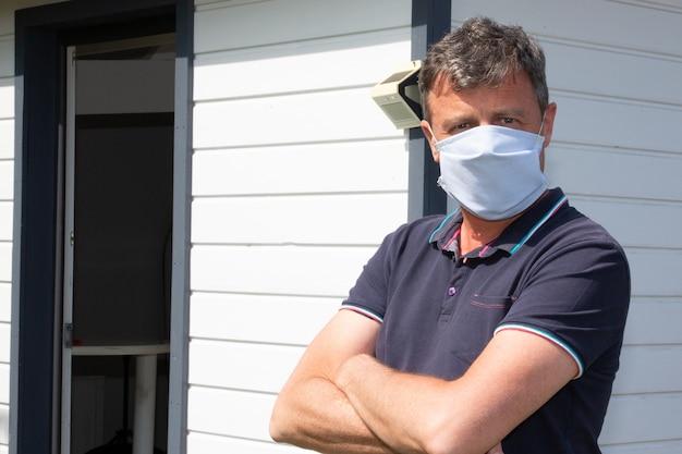 Uomo braccia incrociate indossando tessuto usa e getta in cotone maschera fatta in casa all'aperto contro coronavirus covid-19 virus pericoloso