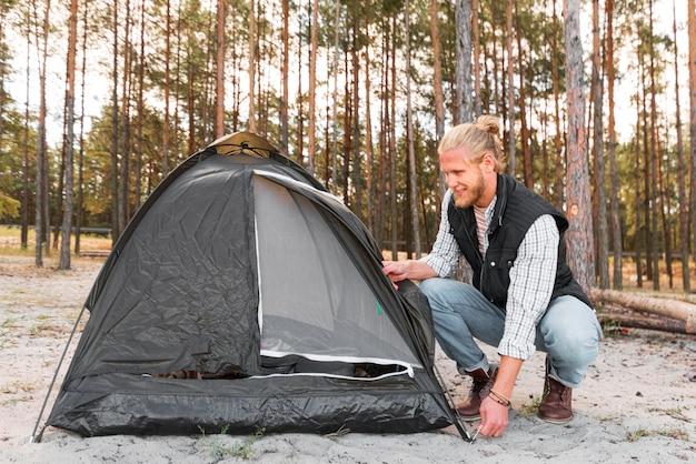 Uomo che organizza la sua tenda nella vista lunga della natura