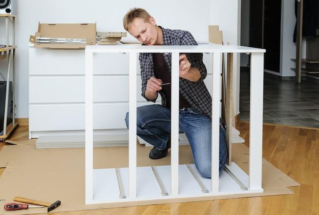 Uomo che monta i mobili a casa che fissa il telaio della cassettiera