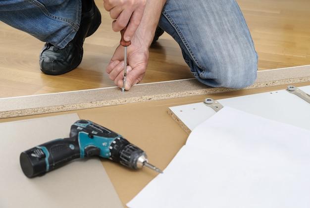 Uomo che monta i mobili a casa ha installato i bulloni del connettore del giunto nel pannello del mobile