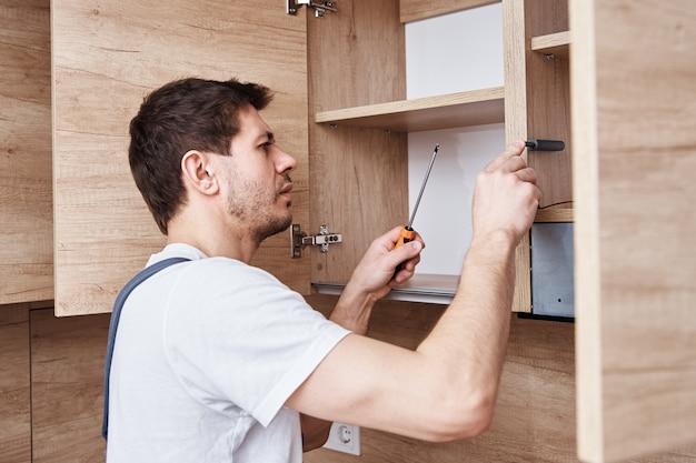 Uomo che monta armadio da cucina