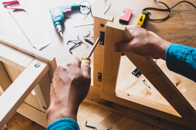 Man montaggio mobili in legno, fissaggio o riparazione di casa con un cacciavite