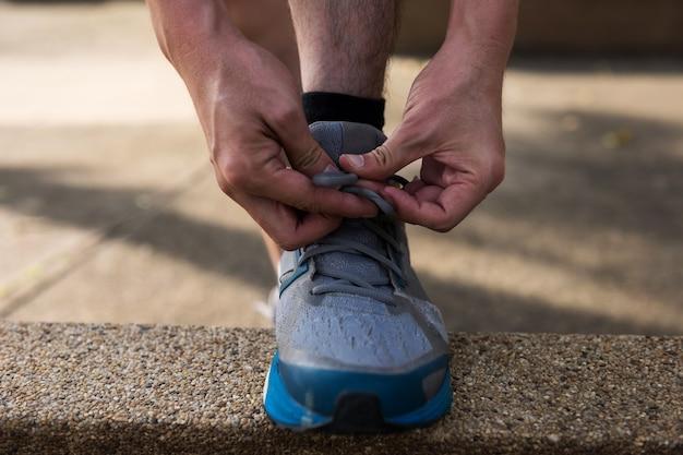 L'uomo atleta runner mani legando scarpe da corsa o lacci delle scarpe sul sentiero con la luce del tramonto prima di correre. bodybuilding e concetto di stile di vita sano.