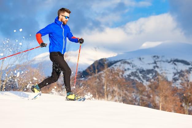 Un atleta uomo si allena per correre con le ciaspole
