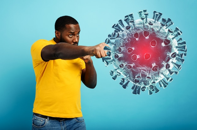 L'uomo attacca con un pugno il coronavirus. parete blu