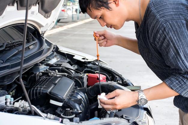 Uomo o meccanico che controlla l'olio del motore dell'auto e la manutenzione prima di viaggiare per motivi di sicurezza.
