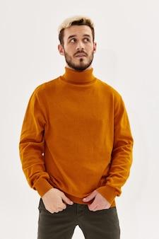L'uomo in abiti autunnali guarda da parte sfondo chiaro di moda