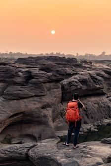 Uomo con lo zaino in spalla che scatta una foto con la macchina fotografica in cima alla roccia nella grande roccia di sam phan bok e nel canyon dei fori al tramonto