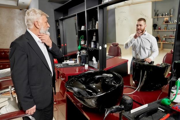 Uomo nel negozio di barbiere vedendo allo specchio riflesso del giovane.