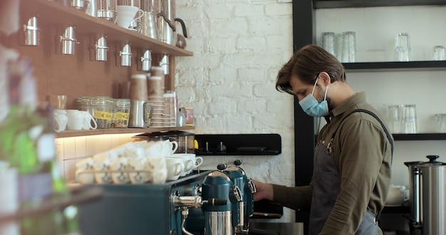 L'uomo barista in maschera facciale sta facendo un cappuccino in un bar caffetteria. concetto di restrizioni sociali di blocco durante la pandemia di covid-19 nei ristoranti.