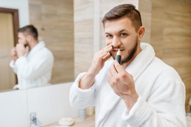 L'uomo in accappatoio rimuove i peli del naso in bagno, igiene mattutina di routine.