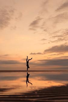 Uomo sulla spiaggia che fa yoga o si allena a pratiche fisiche e respiratorie nella spiaggia della matassa della natura a