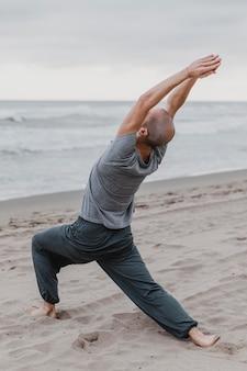 Uomo sulla spiaggia a praticare yoga meditazione