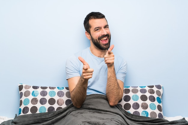Uomo a letto che punta verso la parte anteriore e sorridente